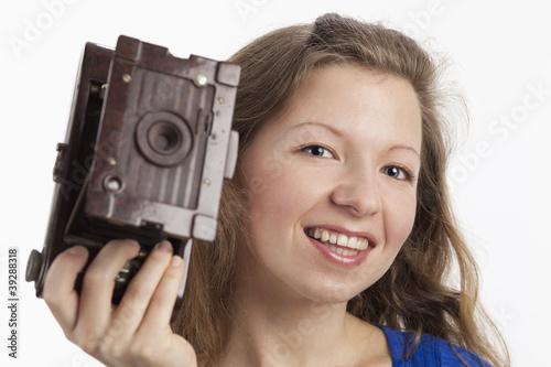 Lächelnde Frau zeigt alten Fotoapparat