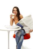 glückliche junge frau mit zeitung und einem glas latte macchiato