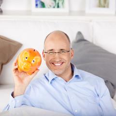 lachender mann hält sein sparschwein in der hand