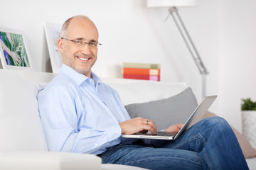 mann arbeitet zuhause mit seinem laptop