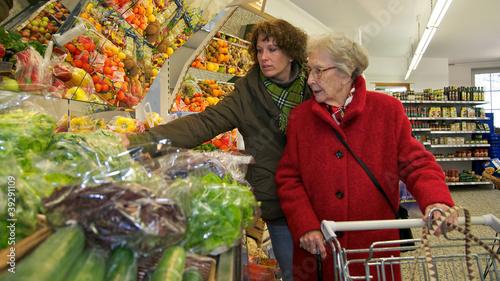 Leinwandbild Motiv Ältere Dame beim einkaufen mit Betreuerin