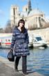 Beautiful brunette tourist walking at the emankment in Paris