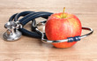 Medical stethoscope and red apple on wooden background
