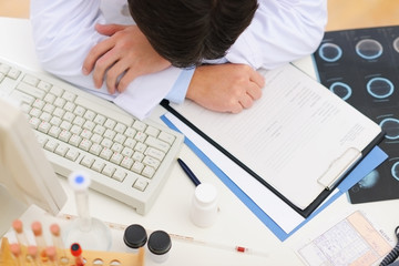 Closeup on tired medical doctor sleeping on table