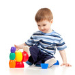 Funny little child is playing with color toys, isolated over whi