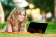 Young woman with laptop at park