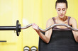 gym: portrait of  young woman lifting weights