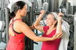 Personal trainer assist senior woman at gym