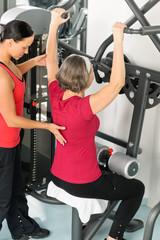 Fitness center trainer senior woman exercise shoulder
