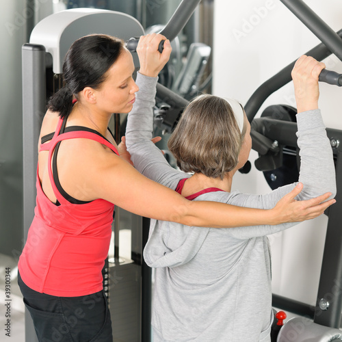 Fitness center trainer senior woman exercise shoulder