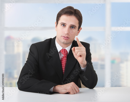 successful business man seriously sitting at a desk in his offic