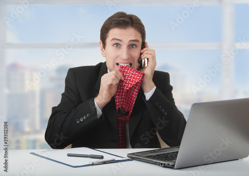 frightened frustrated business man talking on the phone
