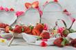 Romantisch gedeckter Tisch mit Herzen, Erdbeeren und Rosen
