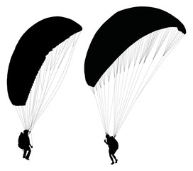 Silhouettes of paraglider on ground preparing before taking off