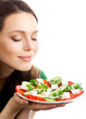 Portrait of happy smiling woman with plate of salad, isolated on