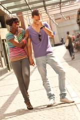 Junges Paar geht händchenhaltend und lächend spazieren