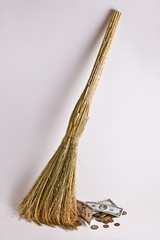 The broom sweeps away money, as if garbage.