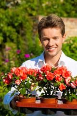 Gartenarbeit im Sommer - Mann mit Blumen