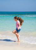 little girl with long brown hair in ponytail in pink t-shirt and poster