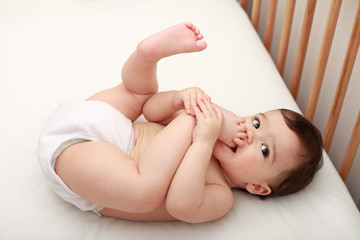 Cute baby sucking his toes in cot