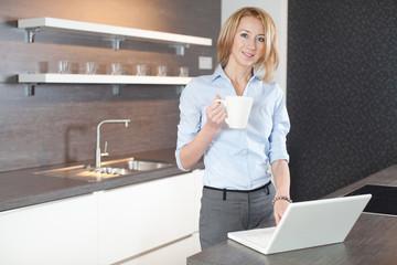 junge frau in der küche mit laptop