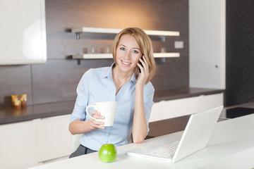 junge frau mit laptop in der küche