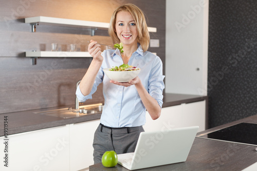 junge frau isst salat in der küche