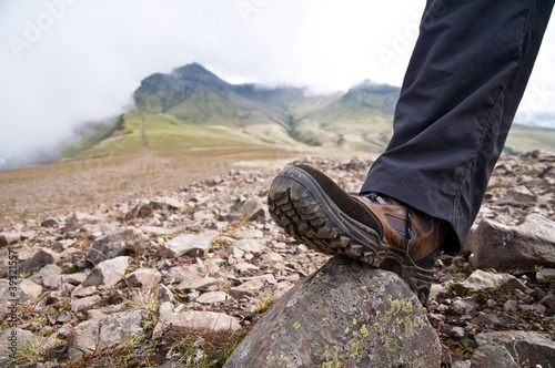 tourist in hiking shoes atop the mountain