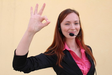 Redhead young woman with headset gesturing OK