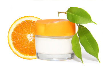 Container of cream and fresh orange fruit isolated.