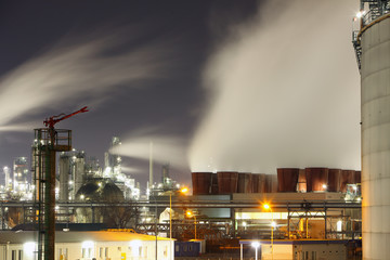 Oil refinery at night with steam/smoke flowing into the sky.