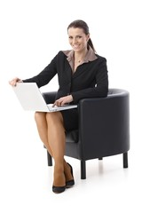 Laughing businesswoman with laptop