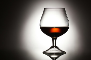 Glass of cognac on grey background
