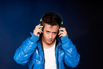 Young man listening music with headphones portrait on blue back