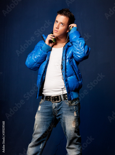 Young man listening music with headphones standing on blue back
