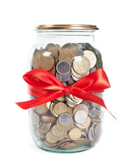 Coins in the jar with red ribbon on white background