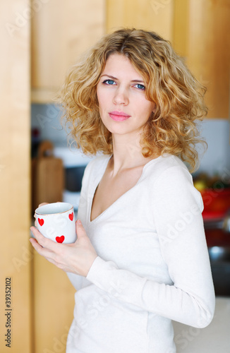 Young woman with a mug of coffee at home