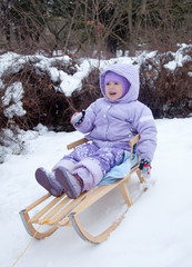 little girl in a winter park on a sled