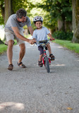 Mid aged man teaching his son to ride a bicycle