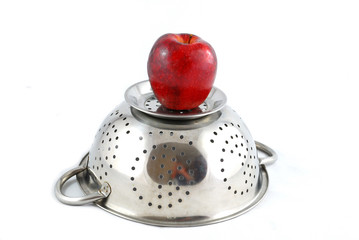 Metal strainer a red apple