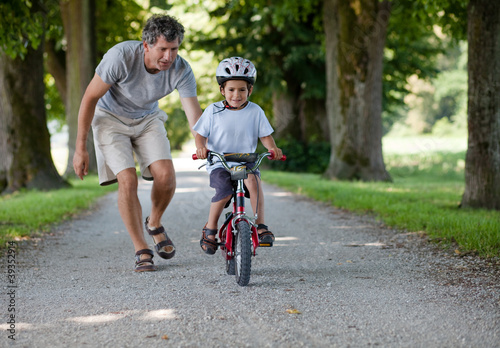Leinwandbild Motiv Father teaching his son to ride a bike