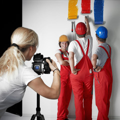 Photoshoot with three workmen painting a white wall