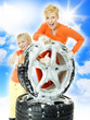 Two sisters cleaning a set of tyres in front of blue sky