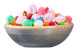 Candy assortment in a wooden bowl, on white background
