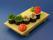 Delicious sushi rolls on wooden plate with ginger and wasabi.