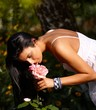 Pretty woman smelling flower in the green
