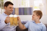 Father and son drinking beer smiling