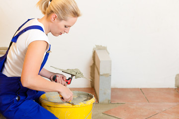 Female tiler tiling tiles on the floor