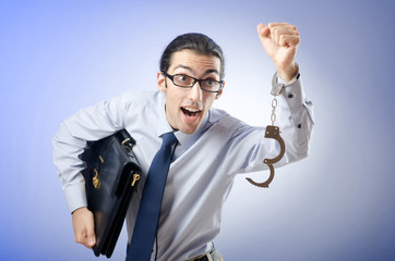 Businessman with handcuffs running away