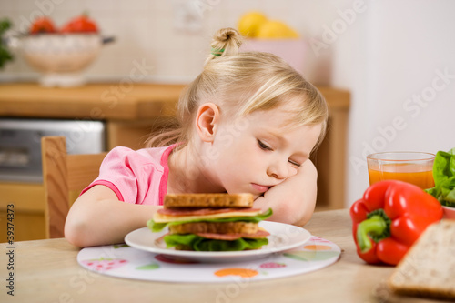 little girl eating? sandwich